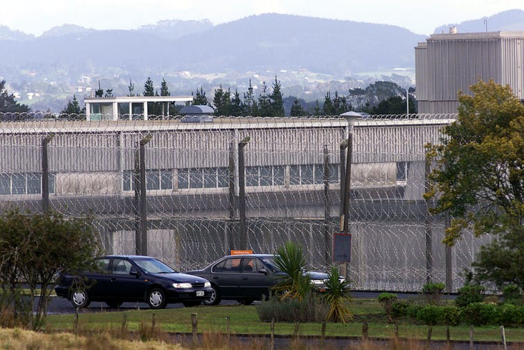 exterior of prison with high fence and concrete walls