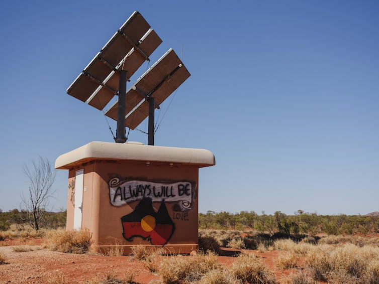 Satellite dish in Uluru with a painted Aboriginal flag saying