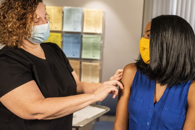 A female health-care worker applies a bandaid to a woman's arm.