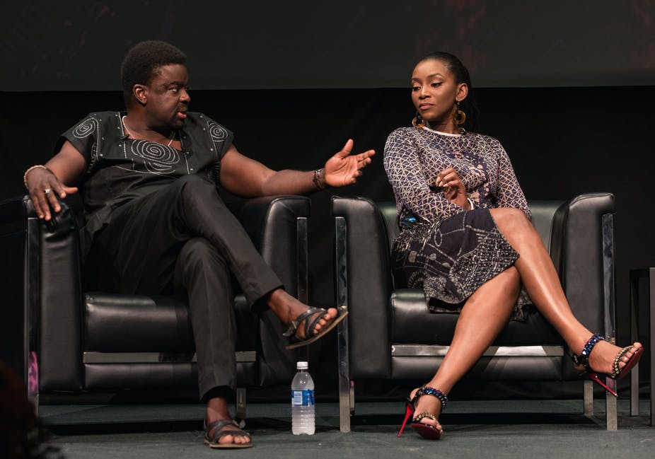 A man and woman seated on a chair side-by-side and having a conversation