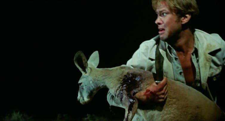 Production image: a man holds a bleeding kangaroo.