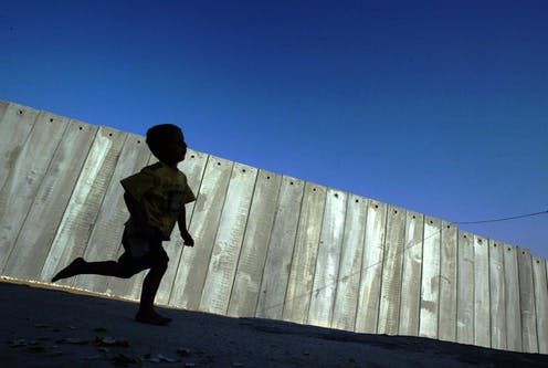 A young Palestinian boy playing in the shadow of the 'security fence' between Israel and the Occupied Palestinian Territory