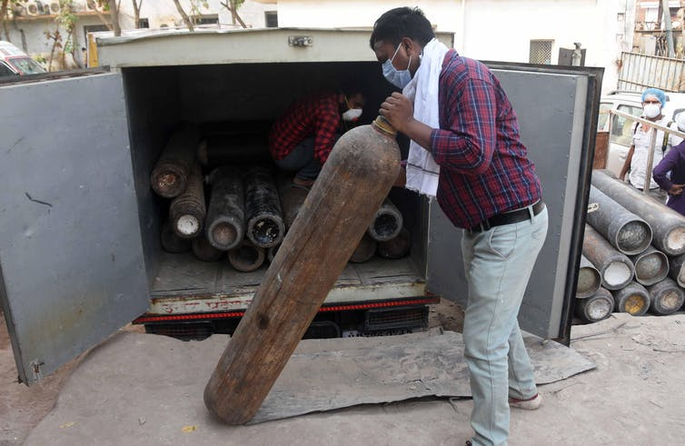A man holding an oxygen cylinder, in front of a truck full of them.