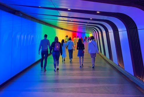 People walking down a rainbow coloured tunnel