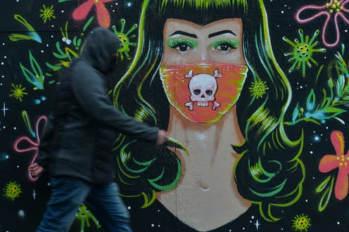 A man in a hoodie walks past a mural of a woman with green hair who wears a mask with a skull and crossbones over the mouth area.