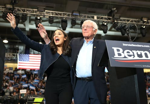 AOC and Sanders wave to the crowd at a rally