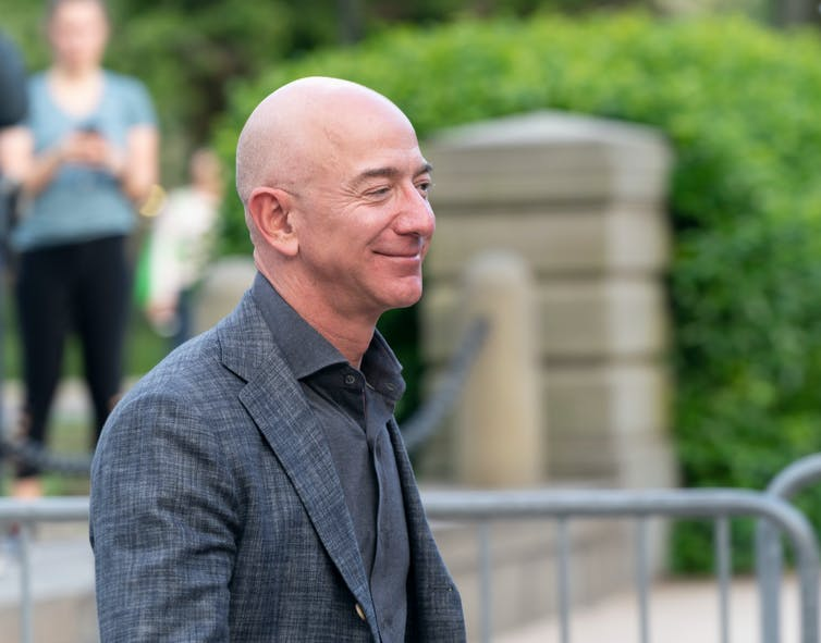 Jeff Bezos stood outside, smiling and wearing a grey suit