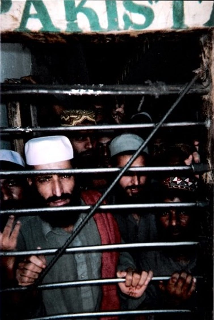 A group of bearded men stand behind a barred door.