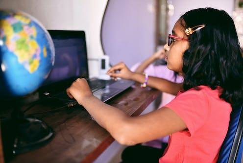 A young girl sits at her computer desk.