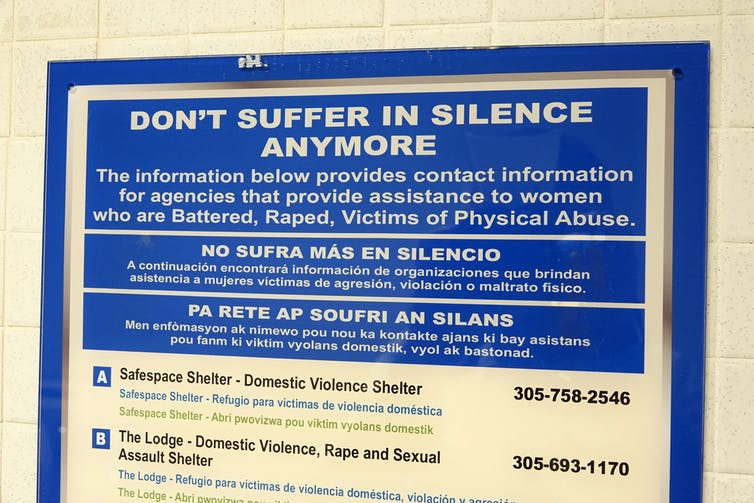 A sign on a wall that provides contact information to help victims of battering, rape and other physical abuse.