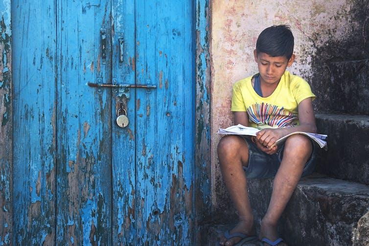 A boy reads a book on a set of steps.