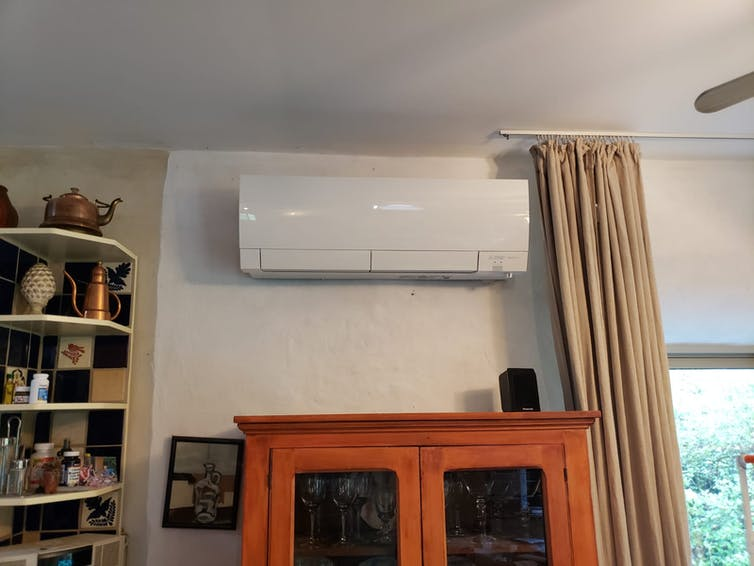Mini split heat pump indoor unit mounted over a fireplace.