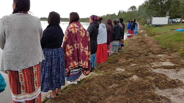 Women stand in a row looking out at a lake.