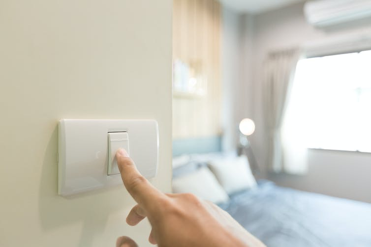 hand turns off light switch in bedroom