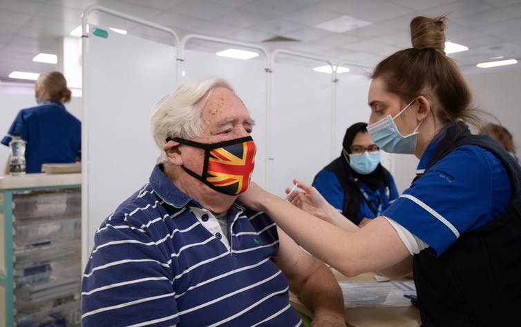 An 84 year old man receives a COVID-19 vaccine in Britain.