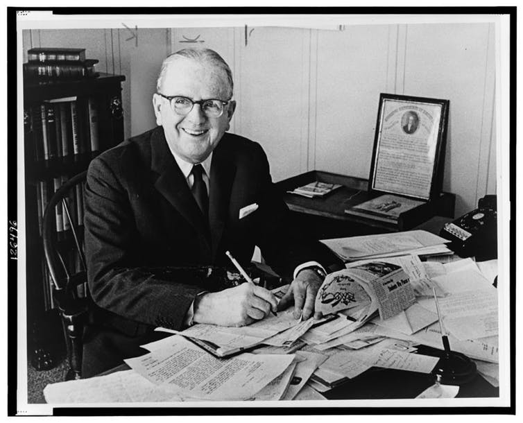A man sits at a desk covered in paper.