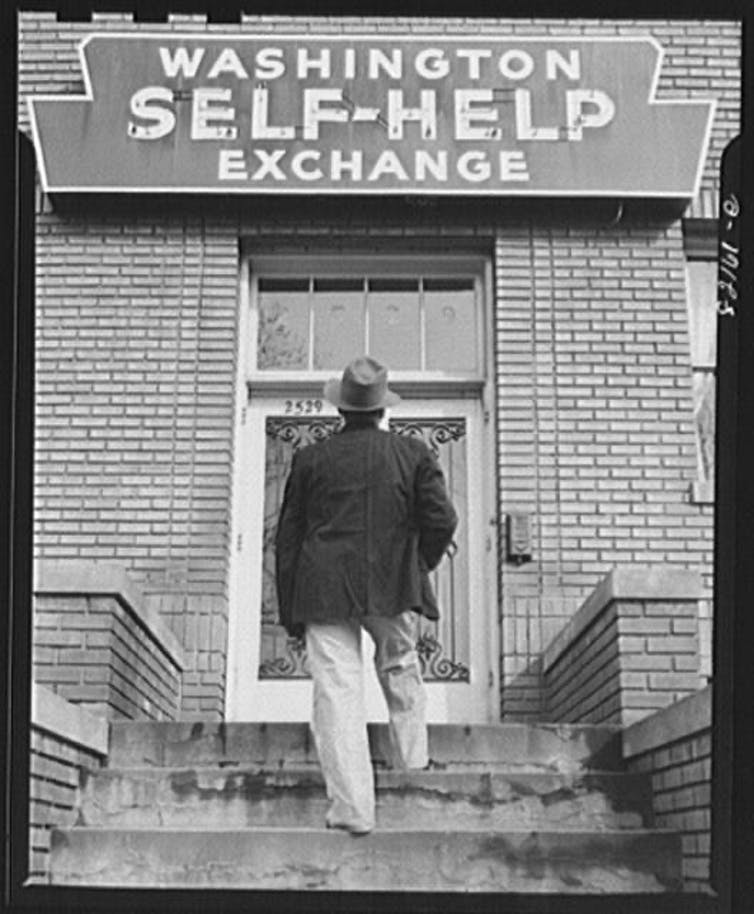 A man walks up to a building: Washington Self-Help Exchange.