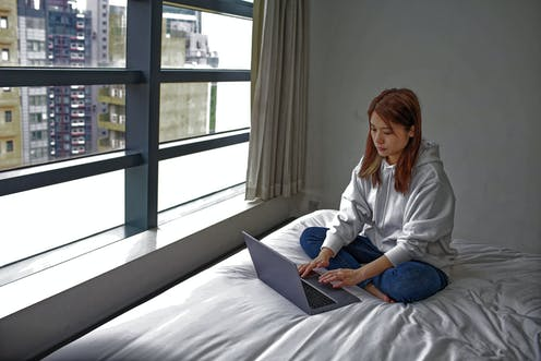 Asian student sitting on bed as she uses laptop