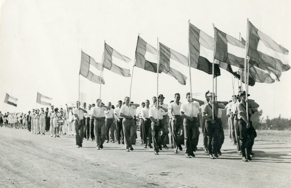 Men wearing shirts with rolled-up sleeves and long pants march with flags hoisted high