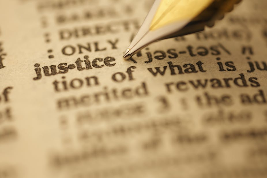 An ink pen pointing at the word 'justice'.