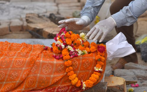 A body is prepared for the last rites at funeral pyres for COVID-19 victims at a makeshift cremation ground in New Delhi