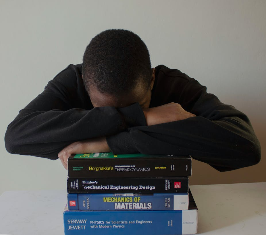 A man in a black shirt hides his face in his folded arms, poised atop a pile of what appear to be university textbooks.
