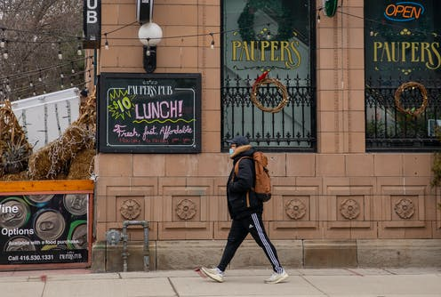 A man strolls past a sign advertising $10 lunch
