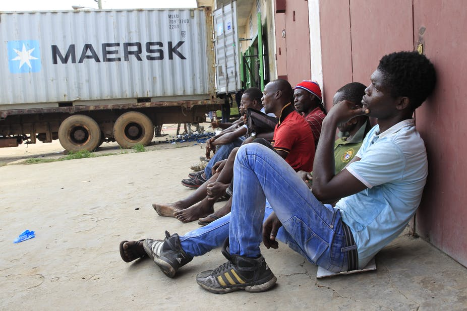 A group of young men seated outside a warehouse with a loading truck nearby.