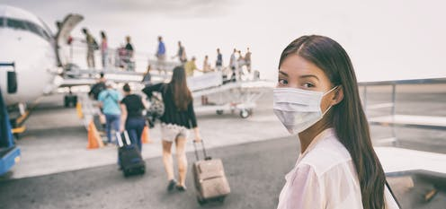 A woman in a face mask looks back as a line of people board a small plane ahead of her