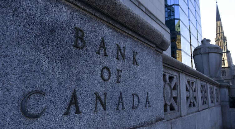 'The Bank of Canada' is etched onto a stone wall.