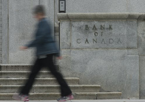 A woman walks past the Bank of Canada