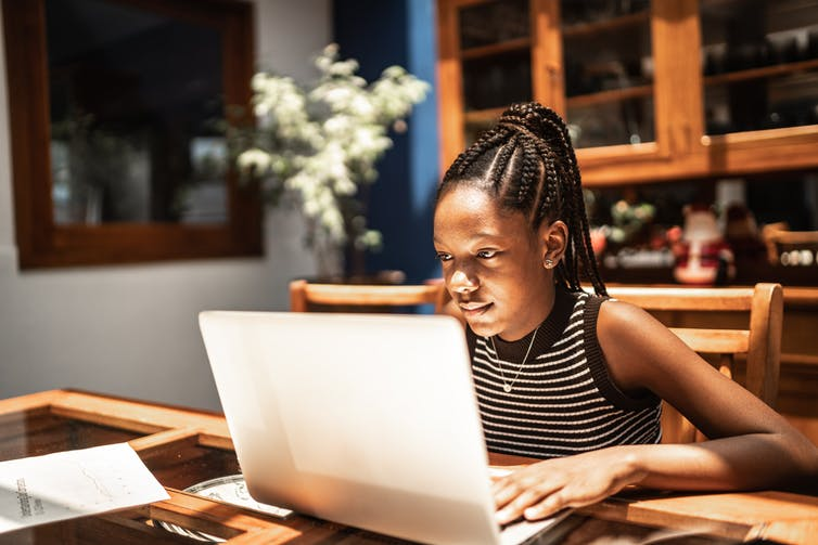 A young African American girl looks at her computer.