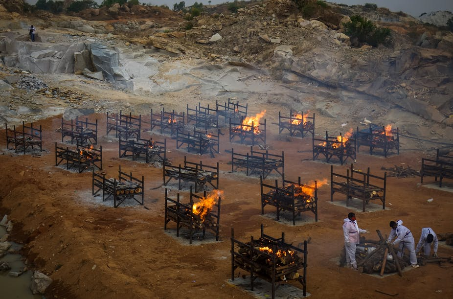 Men wearing PPE performing the last rites at a cremation ground, where mas cremations are being done, Bengaluru, India
