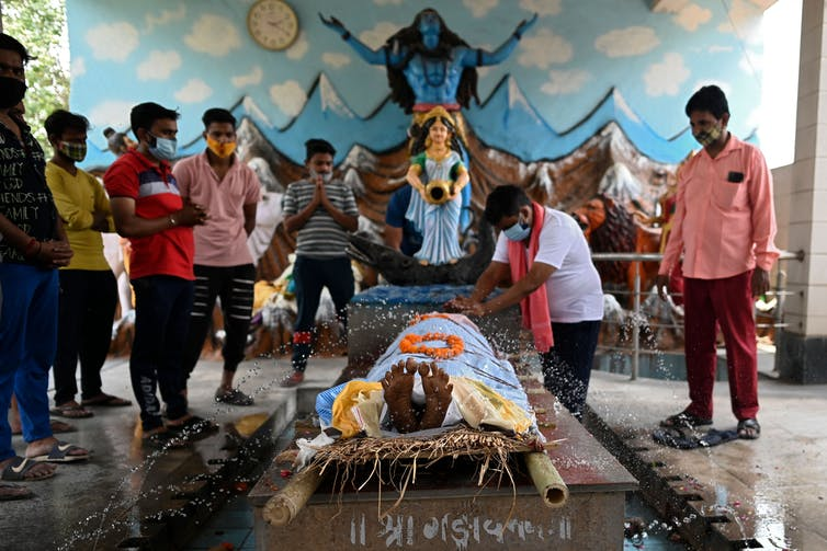 Relatives gather around the body of a man who died of COVID-19 in India, to perform religious rituals.