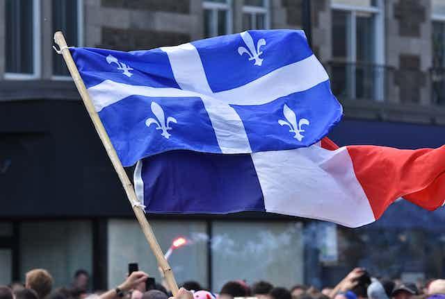 Un drapeau québécois et un drapeau français flottent au vent devant des édifices lors d'une manifestation