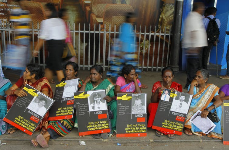 Women sit holding signs