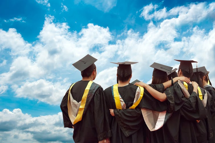 university graduates in academic gowns seen from the back
