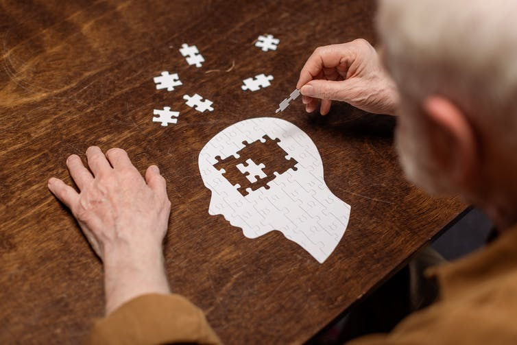Elderly man filling in the brain of a man in a jigsaw puzzle.