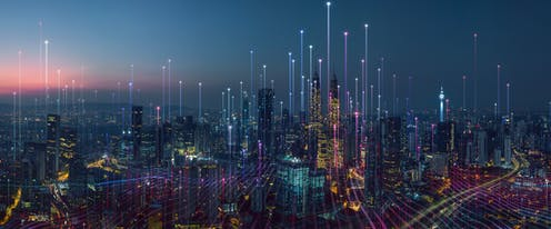 A photo of a city at night time with streaks of light coming out of each skyscraper.