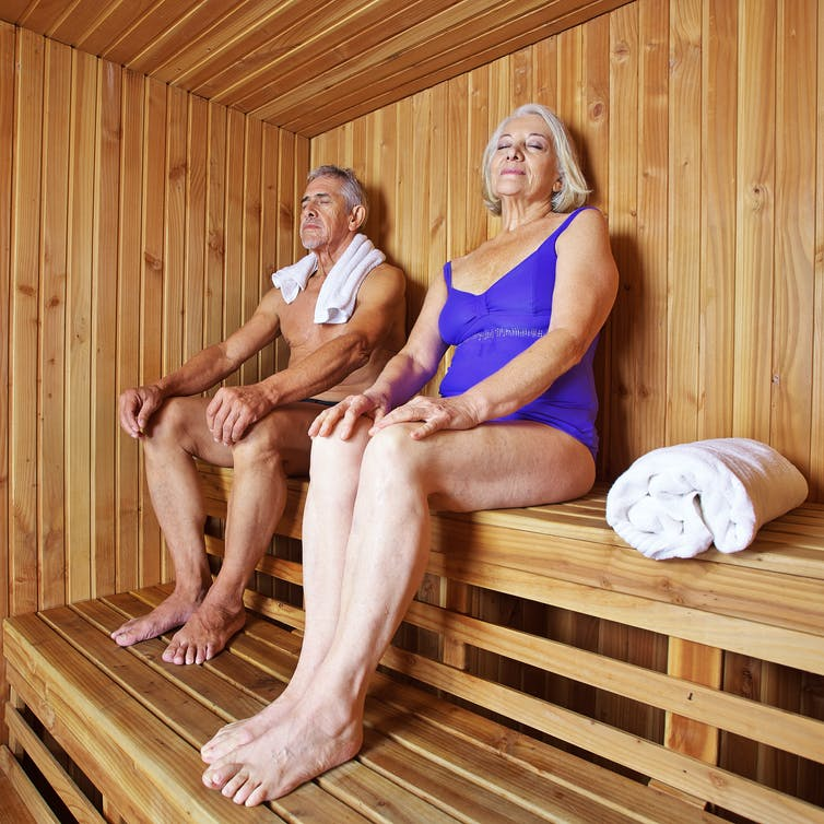 Two older people sitting in wooden sauna, eyes closed.