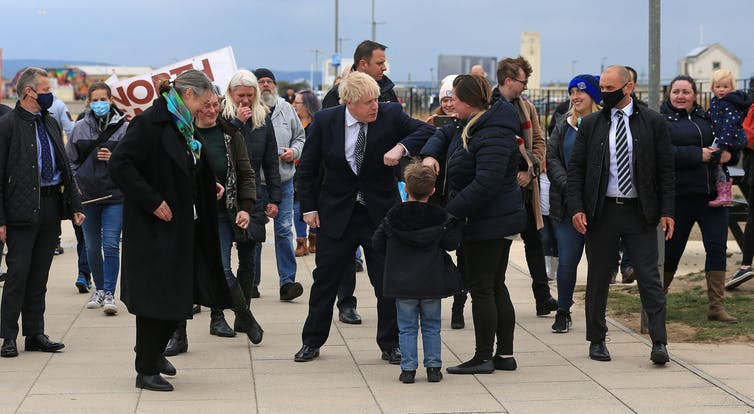 Boris Johnson bumps elbows with a passerby, surrounded by a crowd of people on the sea front in Hartlepool.