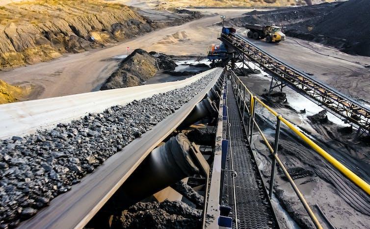 A conveyor belt carrying coal ore in an open-cast mine.