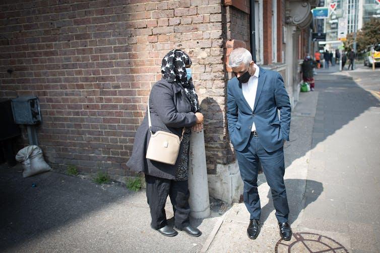 London mayor Sadiq Khan talking to a woman on a London street.