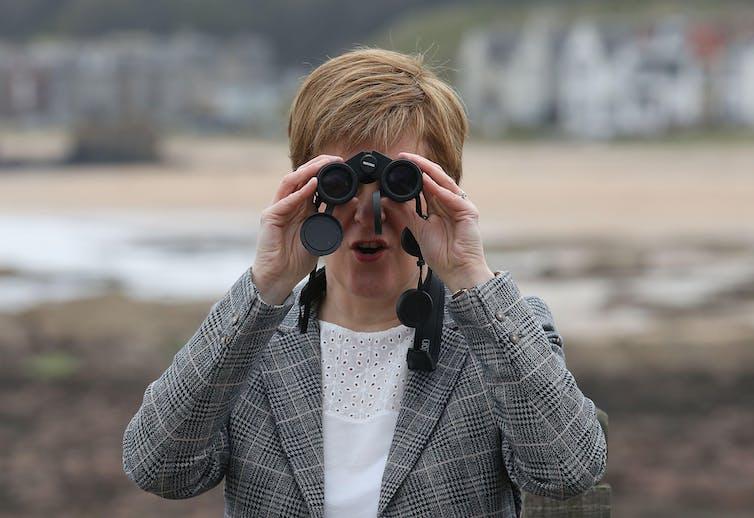 Nicola Sturgeon looking through binoculars.