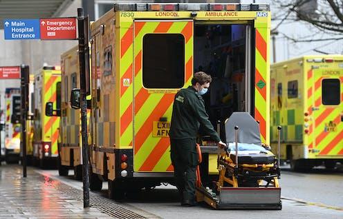 A paramdedic with an empty gurney outside an ambulance.