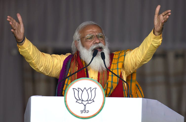 Narendra Modi raises his arms in the air and speaks into microphones at a lectern.