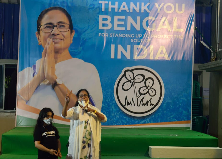 Mamata Banerjee, the chief minister of West Bengal, makes a victory sign in front of an election poster.