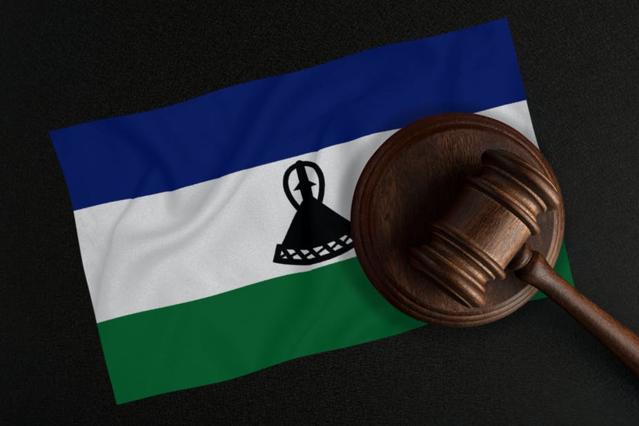 A judge's gavel is superimposed on a flag showing the Basotho traditional straw hat that is the country's national symbol.