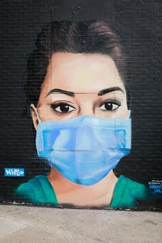Mural of a female health worker wearing scrubs and a surgical mask.