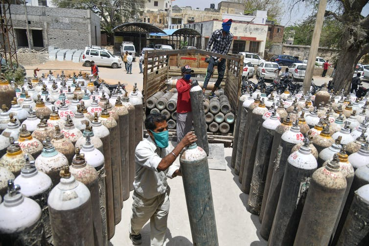 Men loading large oxygen tanks